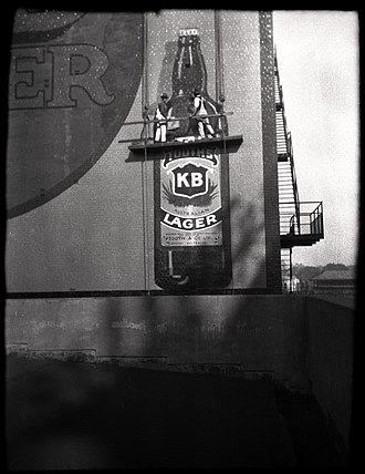 Signwriter - Signwriters painting a KB Lager advertisement on the side of a building in Australia