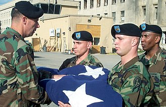 "Joint Force Headquarters National Capital Region - U.S. Army Soldiers from Company A, 3rd Infantry Regiment,""The Old Guard,"" present the Military District of Washington Commander Major General Jim Jackson with the American flag that draped next to the Pentagon's impact site on October 11, 2001."