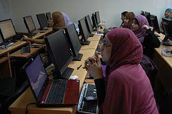 Φοιτήτριες με μαντήλες μπροστά σε υπολογιστές, παρακολουθούν διάλεξη