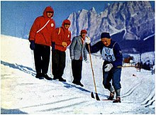 "A man in blue clothes with a number ""33"" cross-country skiing in front of three other men."