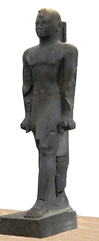 "Statue of Taharqa. His name appears on the center of his belt: 𓇿𓉔𓃭𓈎 (tꜣ-h-rw-k, ""Taharqa""). The statue is 2.7 meters tall. Taharqa has a striding pose, the arms held tight, and holds the mekes staff. He wears a pleated kilt called shendjyt and on the head the double uraeus signifying the double rule over Nubia and Egypt. Kerma Museum.[1]"