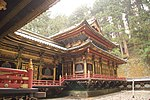 Wooden building connected to a lower building. Both are colored in black and have gilt metal decorations. There is a veranda with red handrail on both buildings.