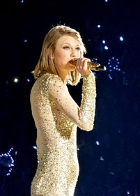 Taylor Swift is performing onstage with a mic in her right hand