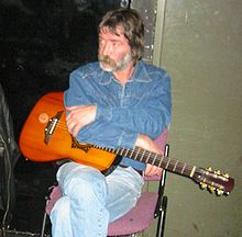 Color photograph of a casually seated middle-aged bearded male wearing casual clothing and resting a guitar on his lap.