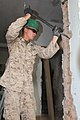 U.S. Marine Corps Lance Cpl. Ryan E. Brake, with the 9th Engineer Support Battalion, 3rd Marine Logistics Group, III Marine Expeditionary Force, breaks off chunks of an inner wall to make room for a door frame 130726-M-DR618-036.jpg