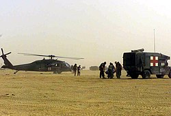 US Navy 030331-M-6910K-021 U.S. Navy Corpsmen transport wounded from an Army Medical Evacuation H-60 Black Hawk helicopter.jpg