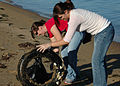US Navy 051014-N-7286M-011 Photographer's Mate 2nd Class Patricia Totemeier and Aviation Survival Equipmentman 2nd Class Jennifer Conard pull a tire out of the water.jpg