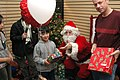 US Navy 061216-N-5067K-061 Air Traffic Controller 1st Class Sean L. Mulvaney holds a gift while Santa passes a present to a young Japanese girl during a Christmas party for two Sasebo-area orphanages.jpg