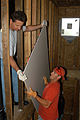 US Navy 070502-N-9604C-001 Two Sailors maneuver a piece of sheetrock through an unfinished wall during a Habitat for Humanity community relations project.jpg