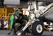 US Navy 070910-N-7883G-009 Airman Luis Estrada, topside petty officer for the waist catapult aboard USS Kitty Hawk (CV 63), verifies that the holdback bar is in place prior to launch