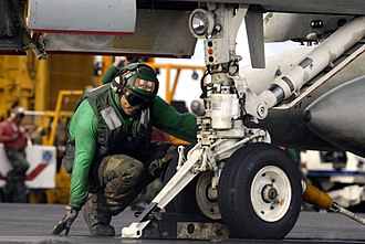 """Aviation boatswain's mate - """"Hookup man"""" ensures that aircraft launchbar (left) and holdback fitting (right) are properly seated in the catapult."""