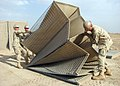 US Navy 090411-N-8547M-025 Seabees assigned to Naval Mobile Construction Battalion (NMCB) 5 lift a HESCO barrier into alignment during a project at Camp Bastion.jpg
