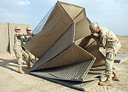 US Navy 090411-N-8547M-025 Seabees assigned to Naval Mobile Construction Battalion (NMCB) 5 lift a HESCO barrier into alignment during a project at Camp Bastion