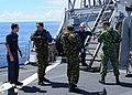 US Navy 111014-N-UE250-547 Fire Controlman 3rd Class Aleksey Yatskovskiy, left, translates for Russian sailors as they perform a visit, board, sear.jpg