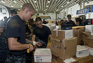 US Navy 111212-N-DX615-013 Logistics Specialist 3rd Class George Vonada scans mail aboard the amphibious assault ship USS Makin Island (LHD 8).jpg