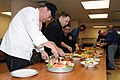 US Navy 120127-N-GU530-123 dam Weiner, left, helps Sailors serve specially prepared dishes during lunch at Naval Submarine Support Center Bangor.jpg