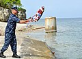 US Navy http-www.navy.mil-management-photodb-photos-100604-N-7764M-030 Capt. Steven Blaisdell, commanding officer of Naval Station Guantanamo Bay, Cuba, tosses a wreath into the bay during a ceremony.jpg