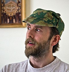 Bearded man in his mid-thirties wearing a camouflage hat