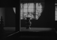 In a semi-darkened room, an ordinary vase is seen on the floor in the background, behind which is a screen upon which the shadows of branches appear