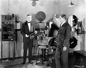 Two suited men stand in a studio with a large film projector and other electrical equipment. The man on the left is holding a large phonograph record.