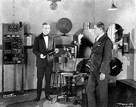 İki takım elbiseli adam, büyük bir film projektörü ve diğer elektrikli ekipmanların bulunduğu bir stüdyoda duruyor.  Soldaki adam büyük bir fonograf kaydı tutuyor.