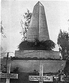 "A large stone obelisk memorial surrounded by white cross grave markers. The original caption reads: ""A memorial erected by the people of Richon le Zion to the memory of the New Zealanders who fell at Ayun Kara on November 14th, 1917."""