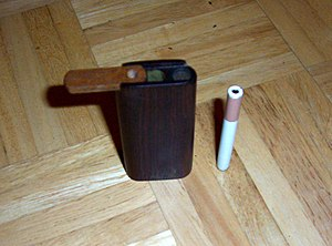 One-hitter (smoking) - Wooden dugout box with cigarette-styled one-hitter, technically a small chillum (with end-to-end channel); in this illustration the sucking end, over which a flexible extension tube can be added, is at top.
