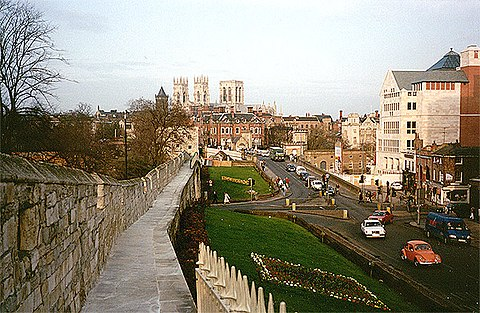 View of the city looking north-east from the city wall, near the railway station. The brown spire in the middle distance is the Catholic church of St Wilfrid, and York Minster is visible behind York city.jpg