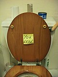 "A yellow post-it note reading ""You lose"" stuck on the underside of a toilet."