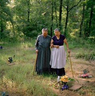 Sapulpa, Oklahoma - Sisters Maxine Wildcat Barnett (left) and Josephine Wildcat Bigler; two of the final surviving elderly speakers of Yuchi, visiting their grandmother's grave in a cemetery behind Pickett Chapel in Sapulpa, Oklahoma. According to the sisters, their grandmother had insisted that Yuchi be their native language.