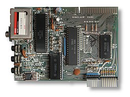 Top-down view of the ZX81 motherboard showing the layout of the components. Four chips are prominent, along with a TV modulator on the top left and a ribbon cable on the bottom right.