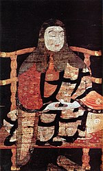 Portrait of a monk in three-quarter view seated cross-legged on a chair. His hands rest, palms up, on his lap in meditating pose.