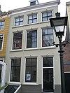 foto van Huis met gepleisterde lijstgevel. Eenvoudige voordeuromlijsting. Dakkapel