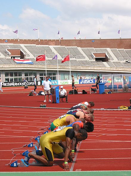 Men assuming the starting position for a sprint race - Track and field