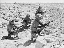 Soldiers crouch behind a low berm amidst a rocky desert area