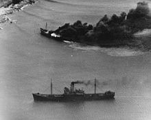 Black and white aerial photo of two ships near a coastline. One of the ships is on fire.