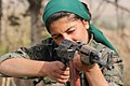 A YPJ fighter aims her rifle.jpg