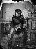 An old woman sitting and wearing a shawl NLW3365021.jpg