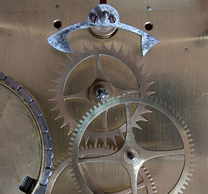 Anchor escapement - The anchor and escape wheel of a late 19th-century clock. The plate that normally holds the front end of the pinions has been removed for clarity. The pendulum is behind the back plate.