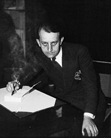 A seated, young, dark-haired man in a suit, photographed from above, is shown writing on a sheet of paper on a desk while staring straight up at the camera.