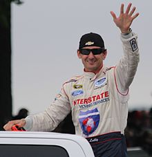 Andy Lally waving 2014 Gardner Denver 200 at Road America.jpg