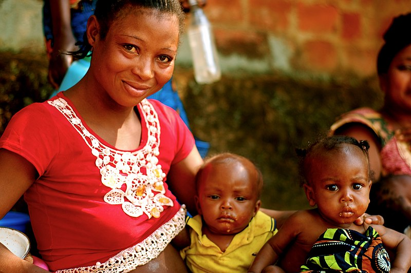 Angolan woman with children outside health clinic (5686703351).jpg