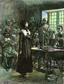 A woman standing before a table behind which are seated several men, with several other men occupying seats against the walls of the room