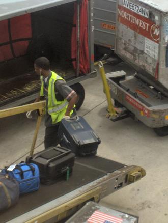 Baggage handler - Unloading baggage from a bag belt