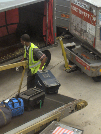 A baggage handler unloading bags from the moto...