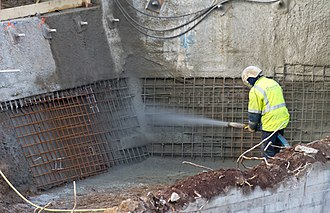 Shotcrete - A building worker is spraying shotcrete on welded wire mesh