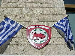 https://upload.wikimedia.org/wikipedia/commons/thumb/b/b8/Blason_et_drapeau_grec_comm%C3%A9moration_jour_du_non.JPG/250px-Blason_et_drapeau_grec_comm%C3%A9moration_jour_du_non.JPG