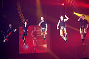Colour photograph of all five members of Boyzone performing in concert in 2009. They are suspended from the ceiling by wires.