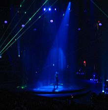 Faraway image of a female performer. She is walking through a water screen that is falling from the ceiling. A blue spotlight is on her, she is wearing blue jeans and a plastic cowboy hat. Green laser lights surround the stage.
