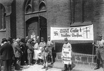 "Stormtroopers holding German Christian propaganda during the church council elections on 23 July 1933 at St. Mary's Church, Berlin. After that, internal struggles, controversies, reorganization, and splits struck the German Evangelical Church Bundesarchiv Bild 183-1985-0109-502, Kirchenwahl.- Propaganda der ""Deutschen Christen"" in Berlin.jpg"
